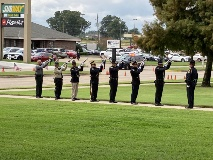 An honor guard fires a 21-gun salute in tribute to fallen officers.